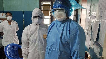 two health care workers in hospital setting with protective suits and masks