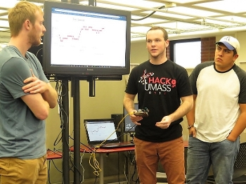 three college students presenting in front of white board in class