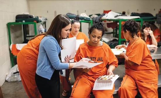 book club at Harris County Prison, women in prison uniforms and one woman in business wear