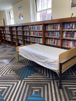 library with wall of bookshelves and bed