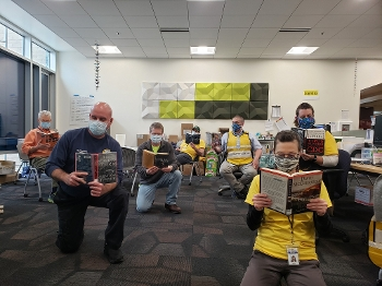 7 men wearing masks, seated or kneeling in library room, reading books