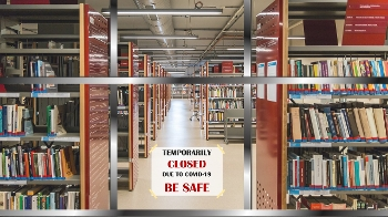 library bookshelves with sign on chain across aisle saying