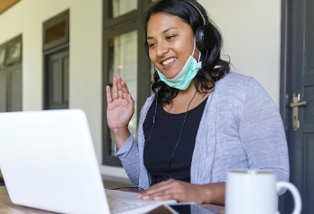 young woman in front of laptop with mask lowered, raising hand