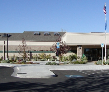 Douglas County Library Minden location exterior, low building with parking lot and flagpole