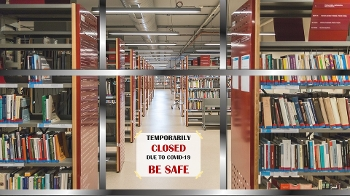 Library shelves holding books with sign across central aisle saying