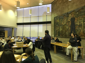 students sitting in chairs and on desks watching man in center lecturing in library with labor-themed mural on one wall