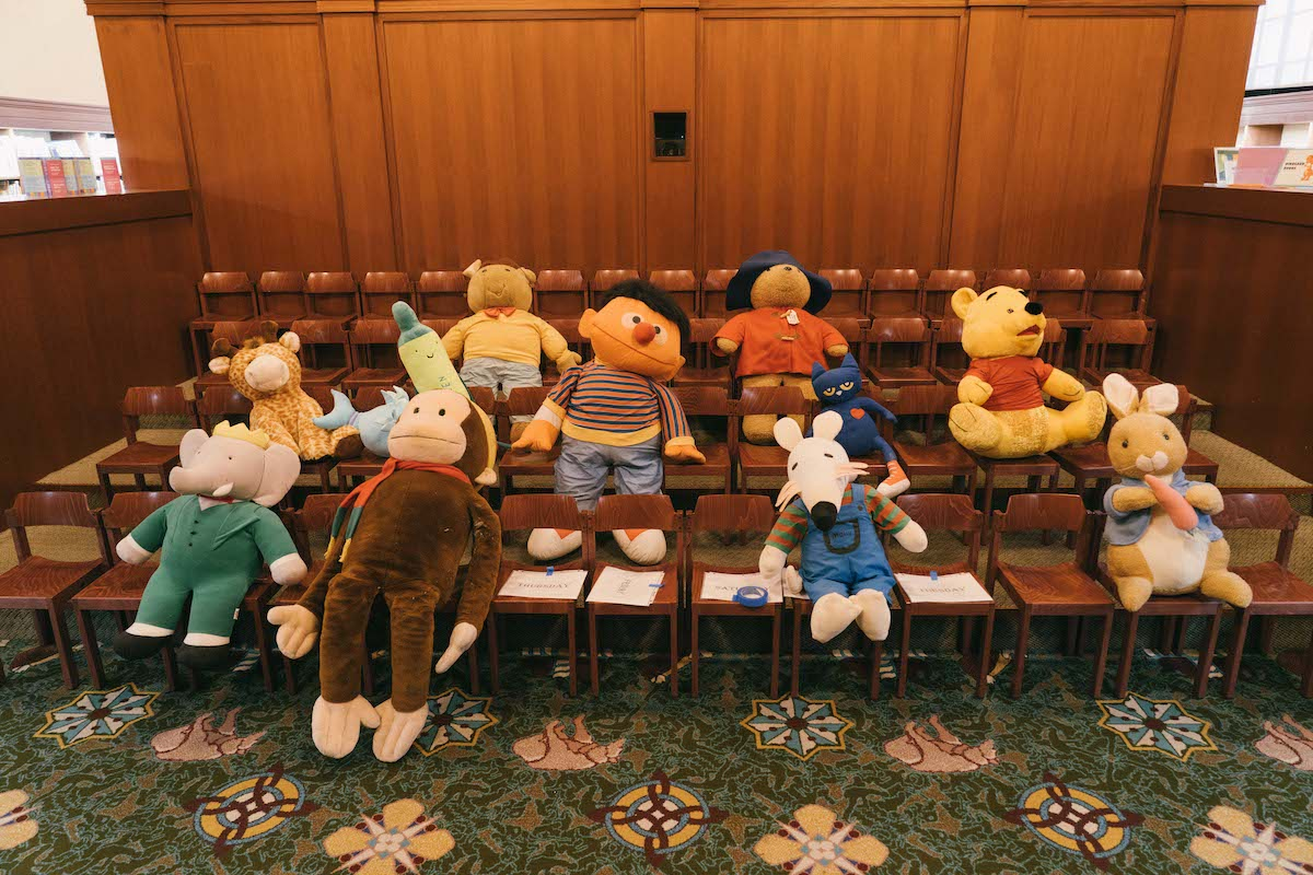 rows of children sized chairs with stuffed animals in them, including Ernie, Peter Rabbit, Winnie-the-Pooh