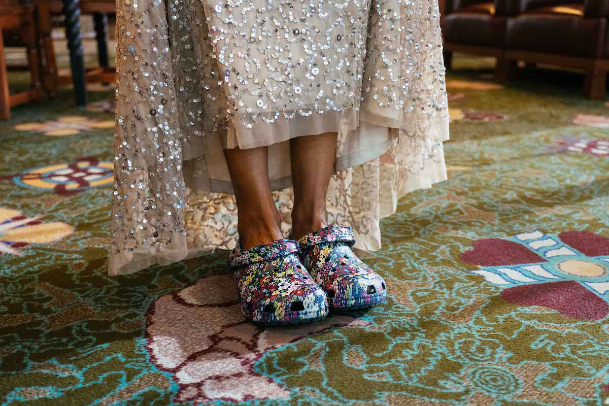 legs emerging from glittery silver long gown, feet in colorful flowered Crocs