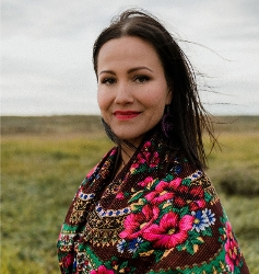Lindsay Knight head shot, woman with black hair and red lipstick in colorful embroidered shawl, standing against horizon