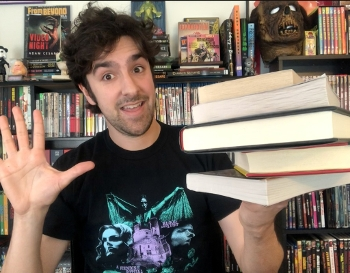 photo of author Adam Cesare holding up a stack of books