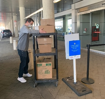 Staff unloading Books For Boston gift from Trident Books in front of a library while wearing a surgical mask due to COVID-19 outbreak
