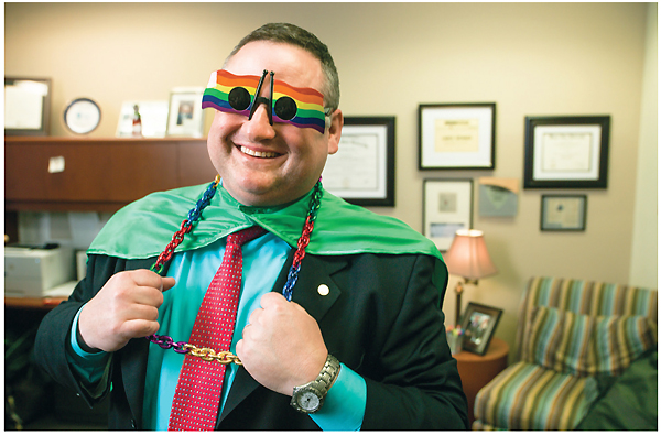 Laughing photo of Lance Werner wearing rainbow flag sunglasses, a cape, and big chain jewelry