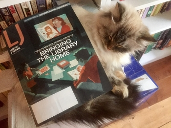 Cat with copy of Library Journal